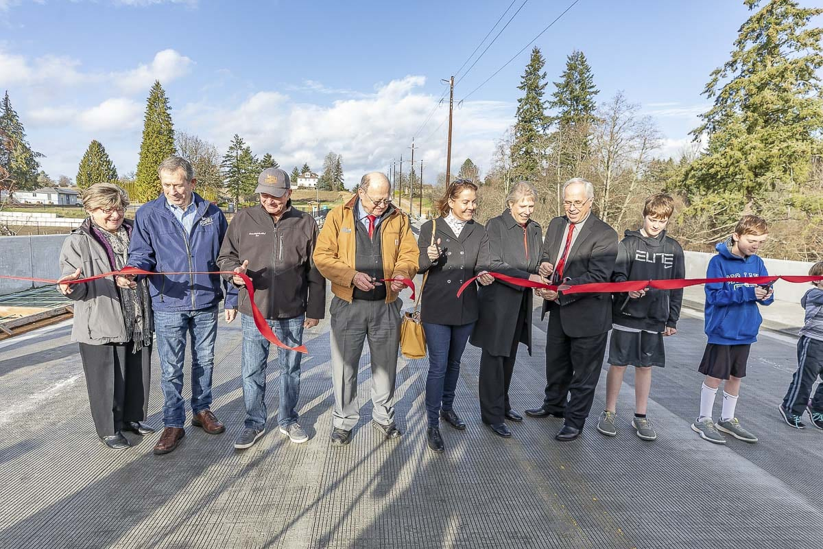 Officials cut the ribbon to mark the end of major construction on the 10th Avenue Bridge across Whipple Creek (from left to right: Ridgefield City Councilor Sandra Day, Ridgefield Mayor Don Stose, Ridgefield City Councilor Ron Onslow, Clark Public Utilities Commissioner Jim Malinowski, State Senator Ann Rivers, Clark County Councilor Julie Olson, Clark County Chair Marc Boldt). Photo by Mike Schultz