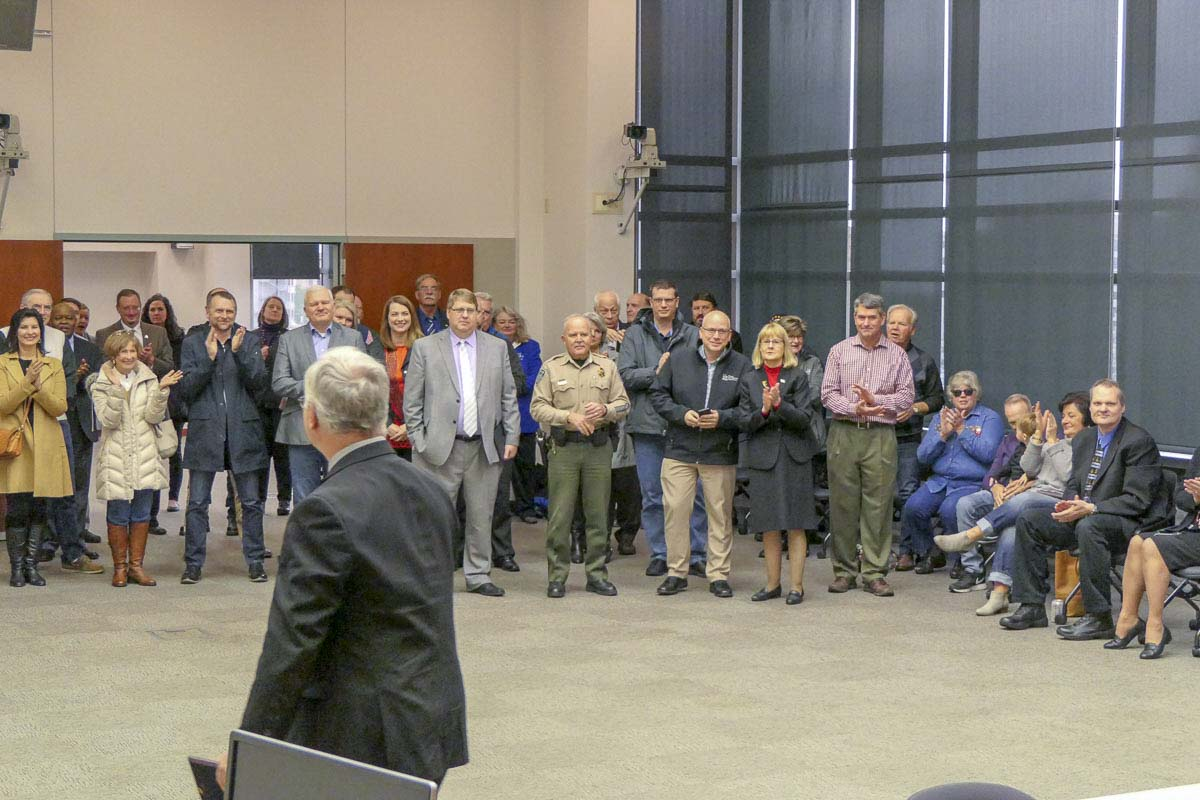 Outgoing Clark County Chair Marc Boldt (foreground) walks off to applause after receiving a certificate recognizing his years of service to the county. Photo by Chris Brown