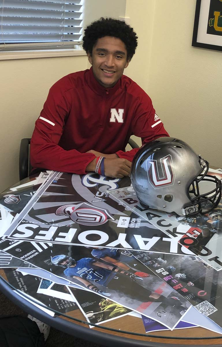 Darien Chase signed his letter of intent to play football at Nebraska while displaying memorabilia from Union football. A senior at Union, Chase helped the Titans win the Class 4A state championship. Now he is preparing to play wide receiver at Nebraska. Photo courtesy of Rory Rosenbach