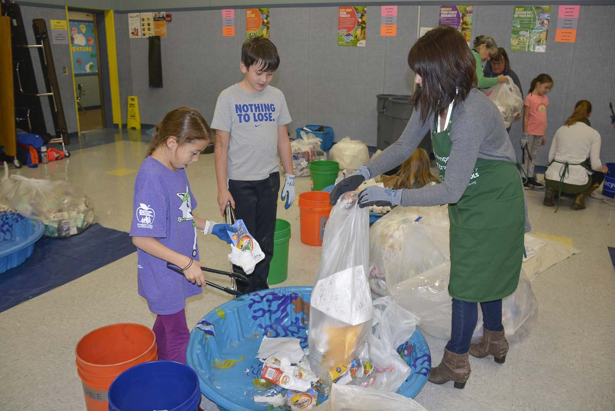 Olive Krysak (left) and Hudson Leifsen (center) help Michelle Picinich (right) from Clark County Green Schools Program sort classroom trash. Photo courtesy of Washougal School District