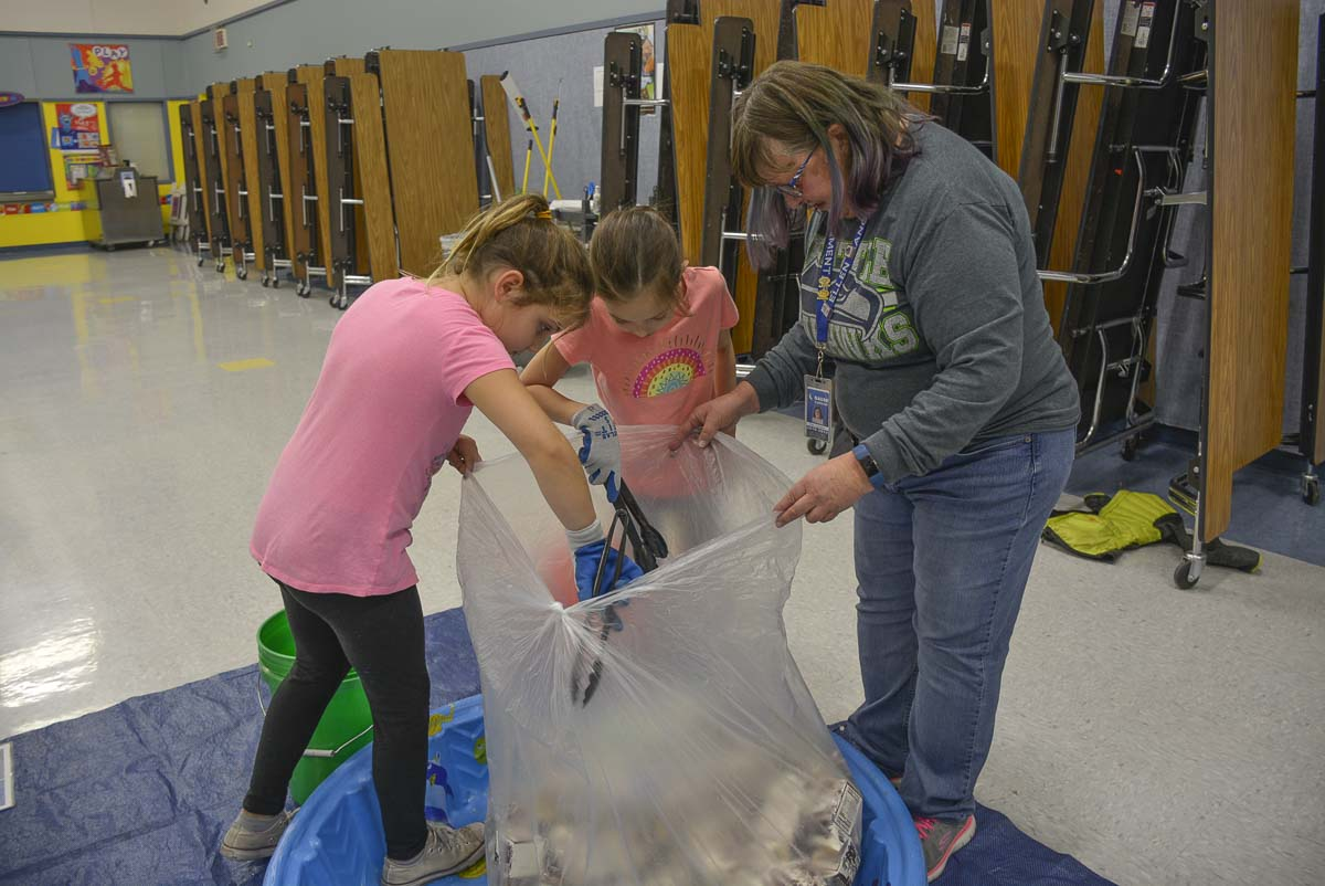Students Parker Forsberg (left) and Kamea Roy (center) help Ellen Lancaster remove items mistakenly sorted in with milk cartons. Photo courtesy of Washougal School District
