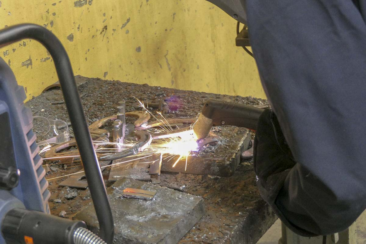 A Ridgefield high school student works at a welding station in metals class. Photo by Chris Brown