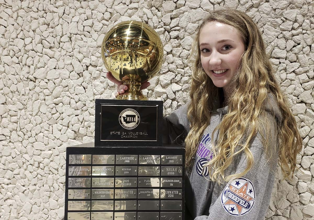 Delaney Nicoll of Ridgefield poses with the Class 2A volleyball state championship trophy. Nicoll helped the Spudders to the title in November and then was voted the 2A state Player of the Year in December. Photo by Paul Valencia