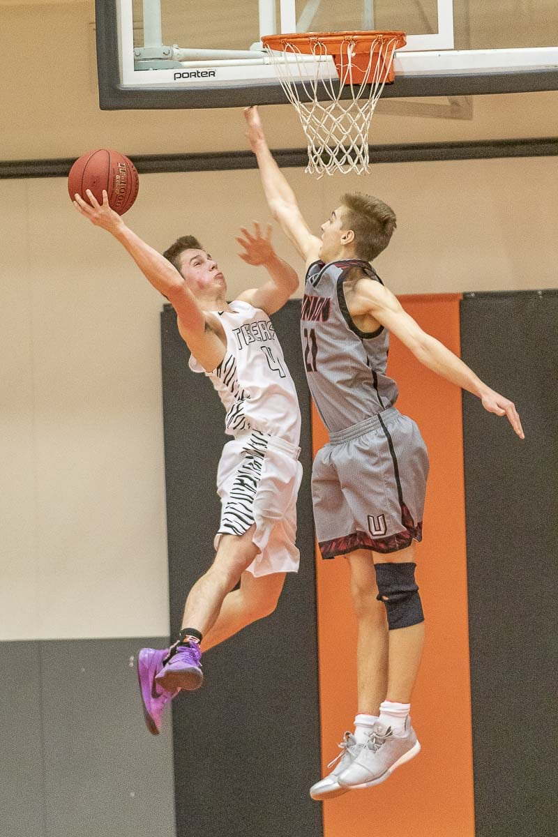 Union's Tanner Toolson (21) skies high to defend against Battle Grounds' Vincent McCormic during Wednesday's game. Toolson had a huge third quarter, igniting the comeback in Union's 57-41 win. Photo by Mike Schultz