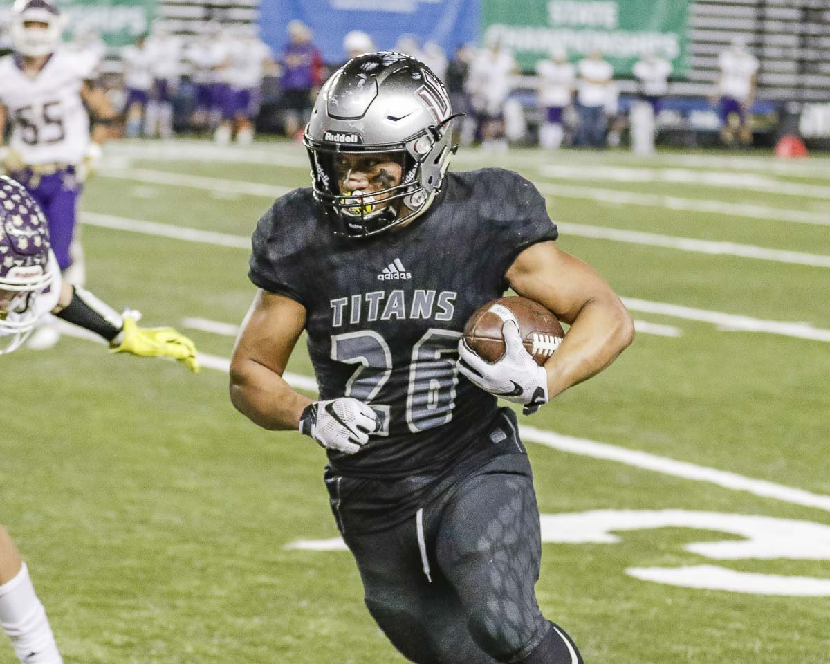 Union running back Jojo Siofele (26) had 292 yards from scrimmage and four touchdowns to help the Titans claim the Class 4A state championship with a 52-20 win over Lake Stevens Saturday at the Tacoma Dome. Photo by Mike Schultz