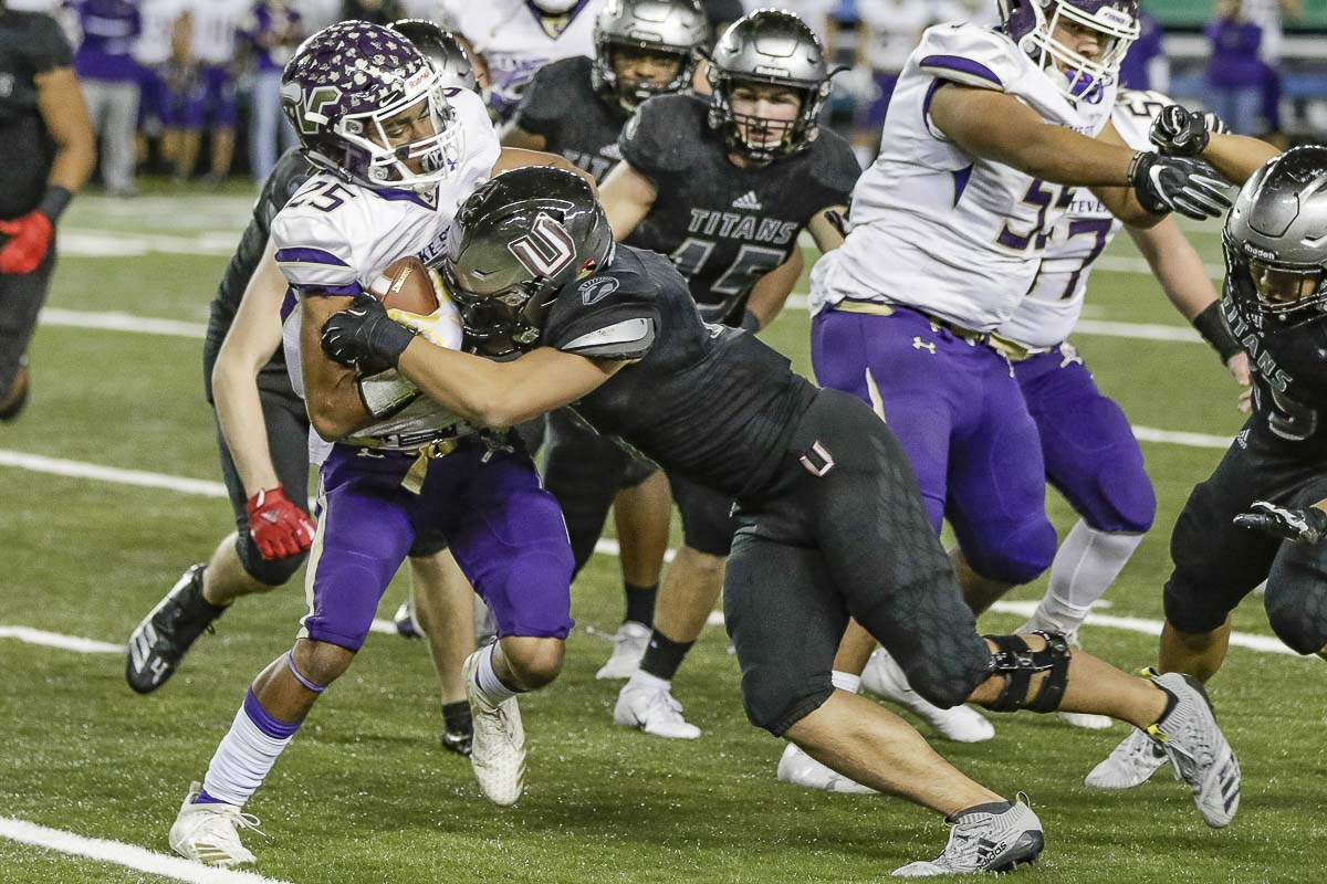 Union defensive back Justin Chin (9) lays a hit on Lake Stevens wide receiver Kasen Kinchen (25) during Saturday's Class 4A state football championship game at the Tacoma Dome. Photo by Mike Schultz