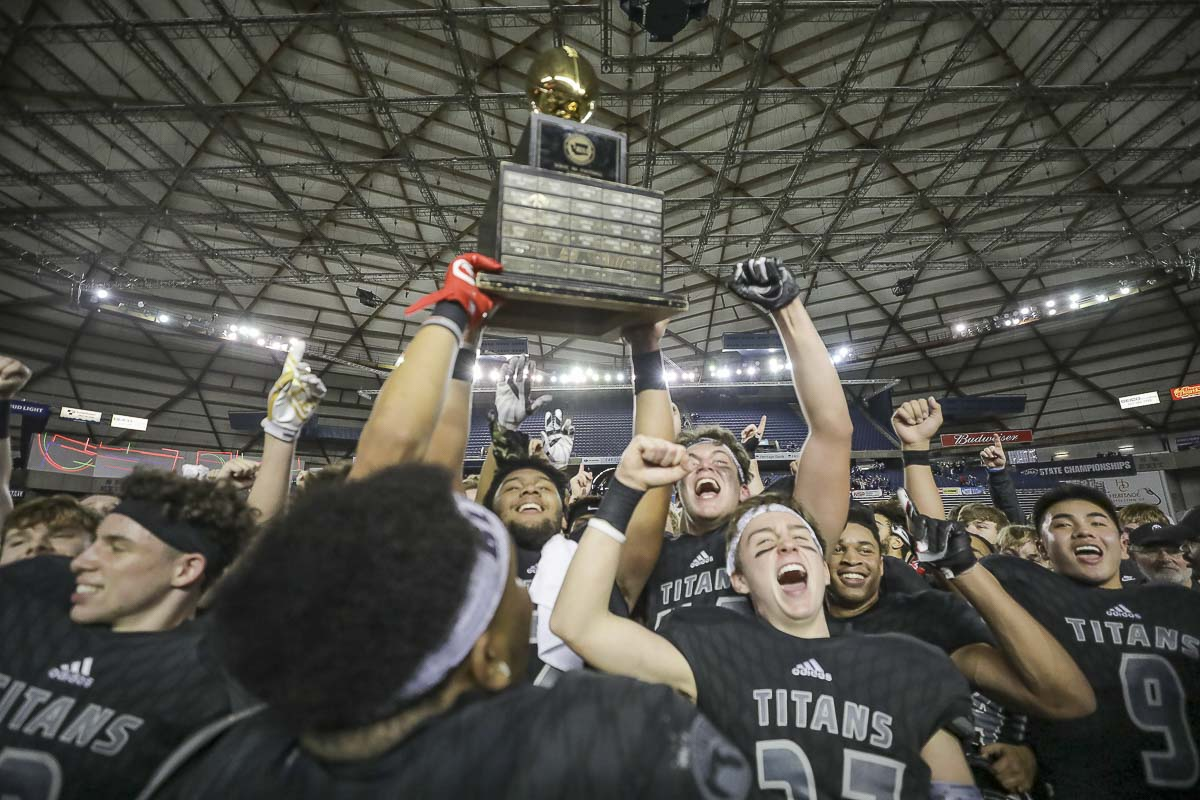 Union football players hoist the Class 4A state championship trophy after the Titans defeated Lake Stevens 52-20 Saturday at the Tacoma Dome. Photo by Mike Schultz