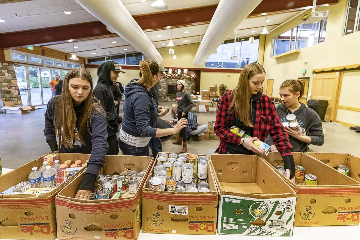 Student volunteers help separate donated food into categories at the Battle Ground Community Center. Much of the involvement of the North County Community Food Bank is centered around the area's school districts, said Board President John Idsinga. Photo by Mike Schultz