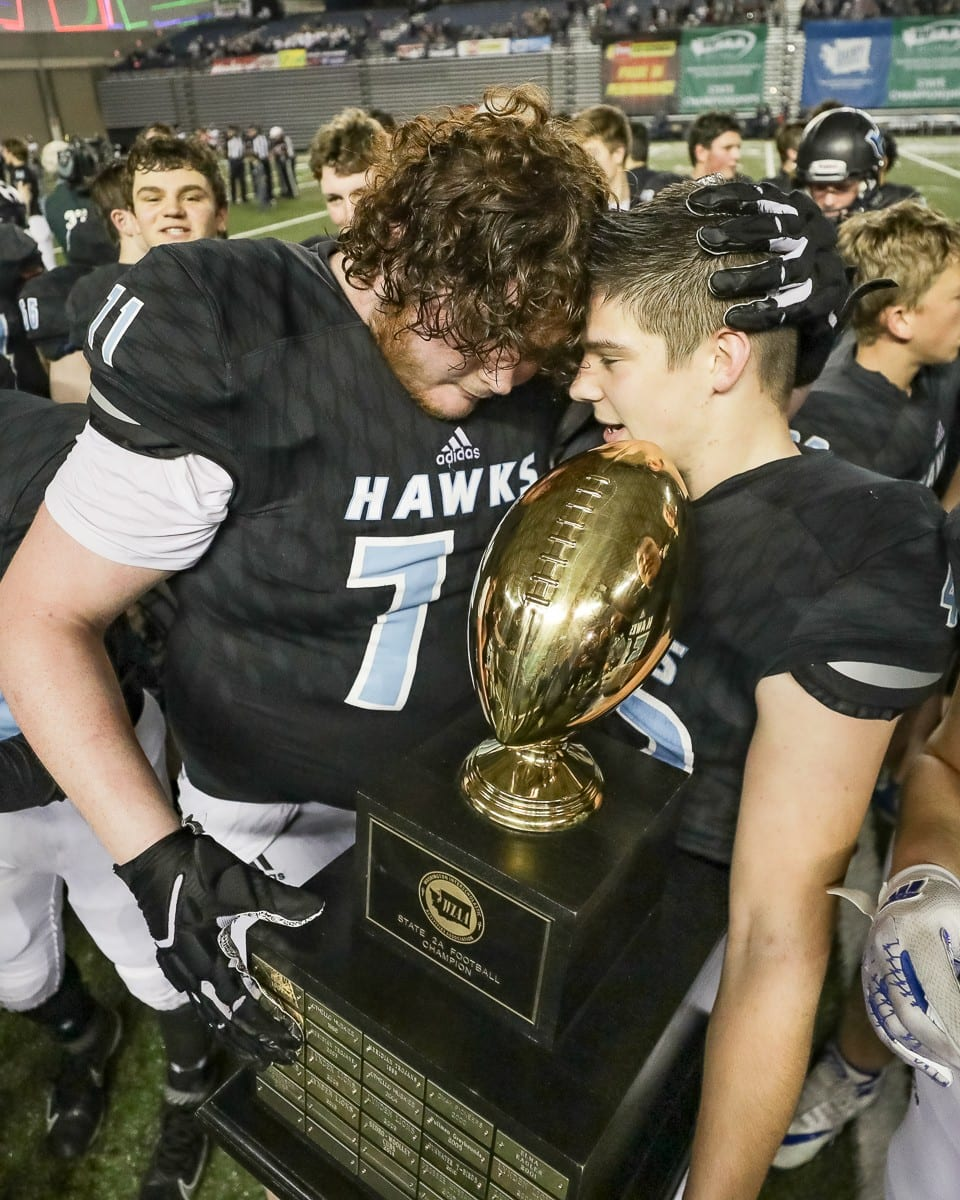 Hockinson players Nathan Balderas (71) and Jonathan Domingos (42) share a special moment with the Class 2A state championship trophy Saturday at the Tacoma Dome. Photo by Mike Schultz
