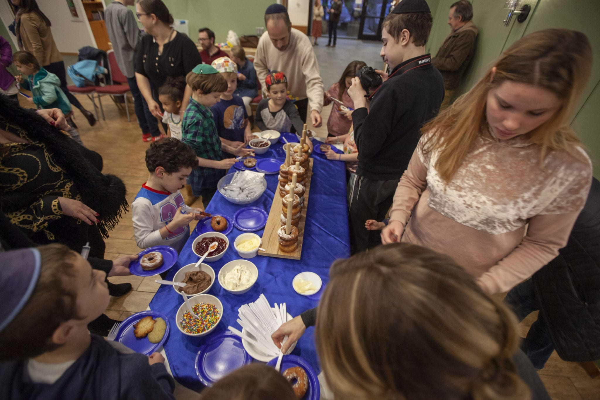 Families gather around to put jelly and toppings on powdered doughnuts during the Chabad Jewish Center's Hanukkah festival for children of all ages. Photo by Jacob Granneman