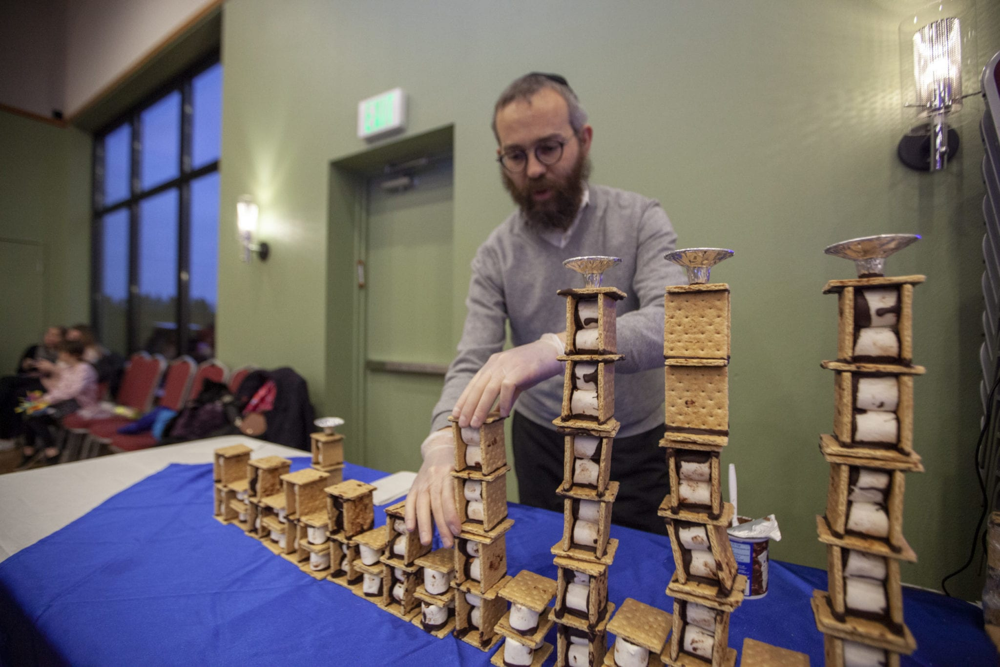 Rabbi Shmulik Greenberg, of the Chabad Jewish Center, assembles a huge menorah made of s'mores at the synagogue's annual kids celebration for Hanukkah. Photo by Jacob Granneman