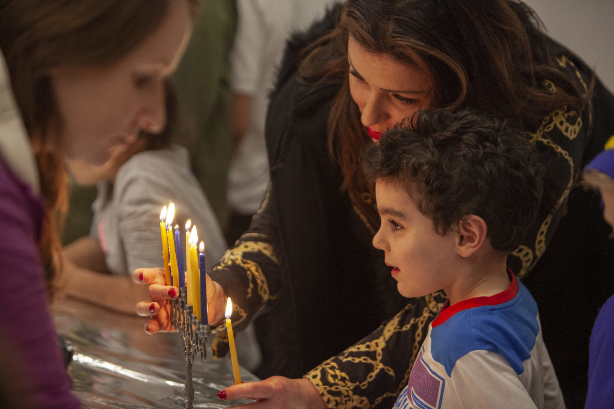 Olgah Goysman and her son Ari light the candles of their family menorah during the children's Hanukkah festival at Chabad Jewish Center on Dec 9. Photo by Jacob Granneman
