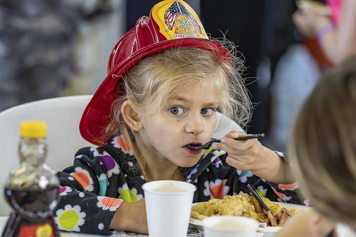 Dahlia Gruenberg enjoys the Pancake Breakfast sponsored by Fire District 3 at the annual Harvest Days Celebration in Battle Ground. Photo by Mike Schultz
