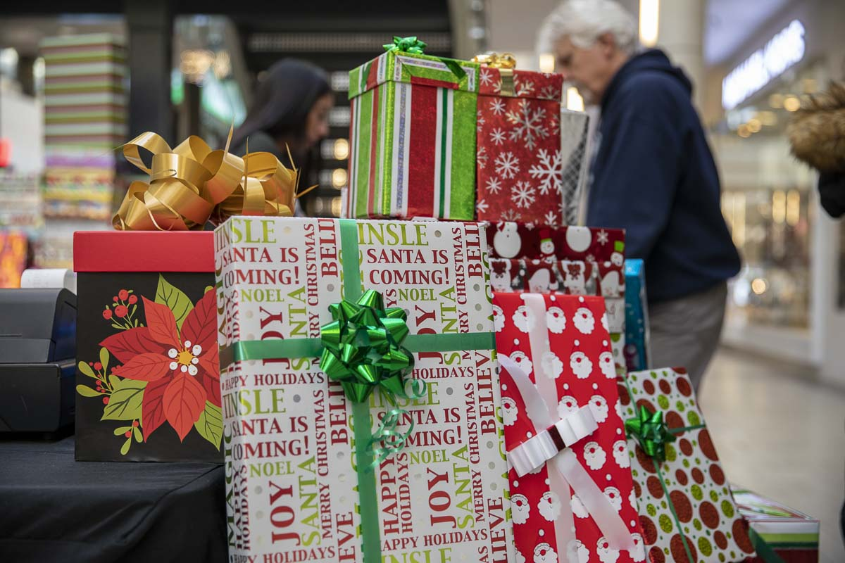 Shoppers take advantage of the professional wrapping skills of folks at the Vancouver Mall, after making their purchases. Tables with all the accoutrements needed are located across the entire mall. Photo by Jacob Granneman