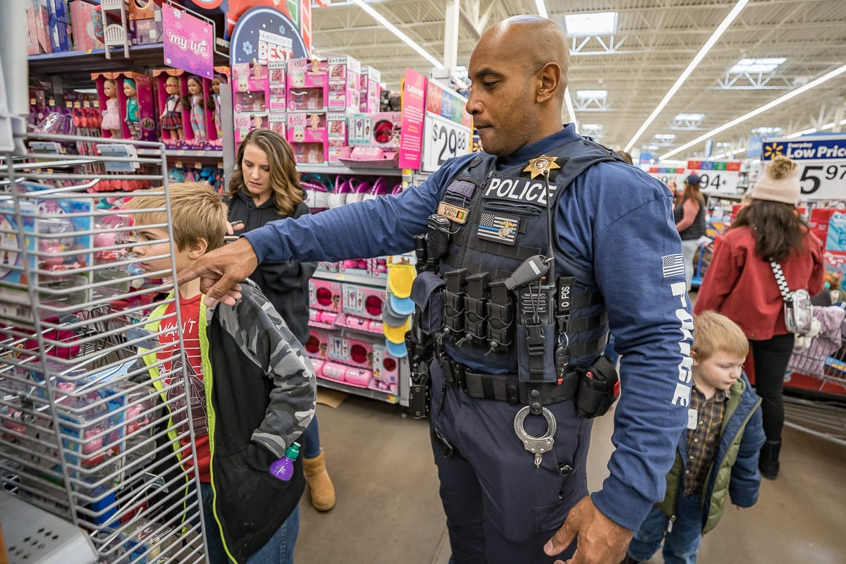 Cowlitz Tribal Police Officer Brandon Molett helps children pick out toys at the eighth annual Shop with a Cop in Woodland. Photo by Mike Schultz