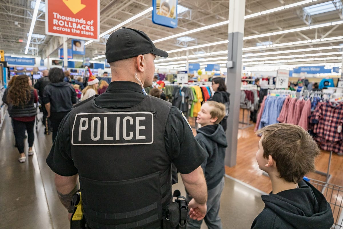 La Center Police Department Officer Alec Langlois takes children through the Woodland Walmart to buy Christmas presents and new winter clothing. Photo by Mike Schultz