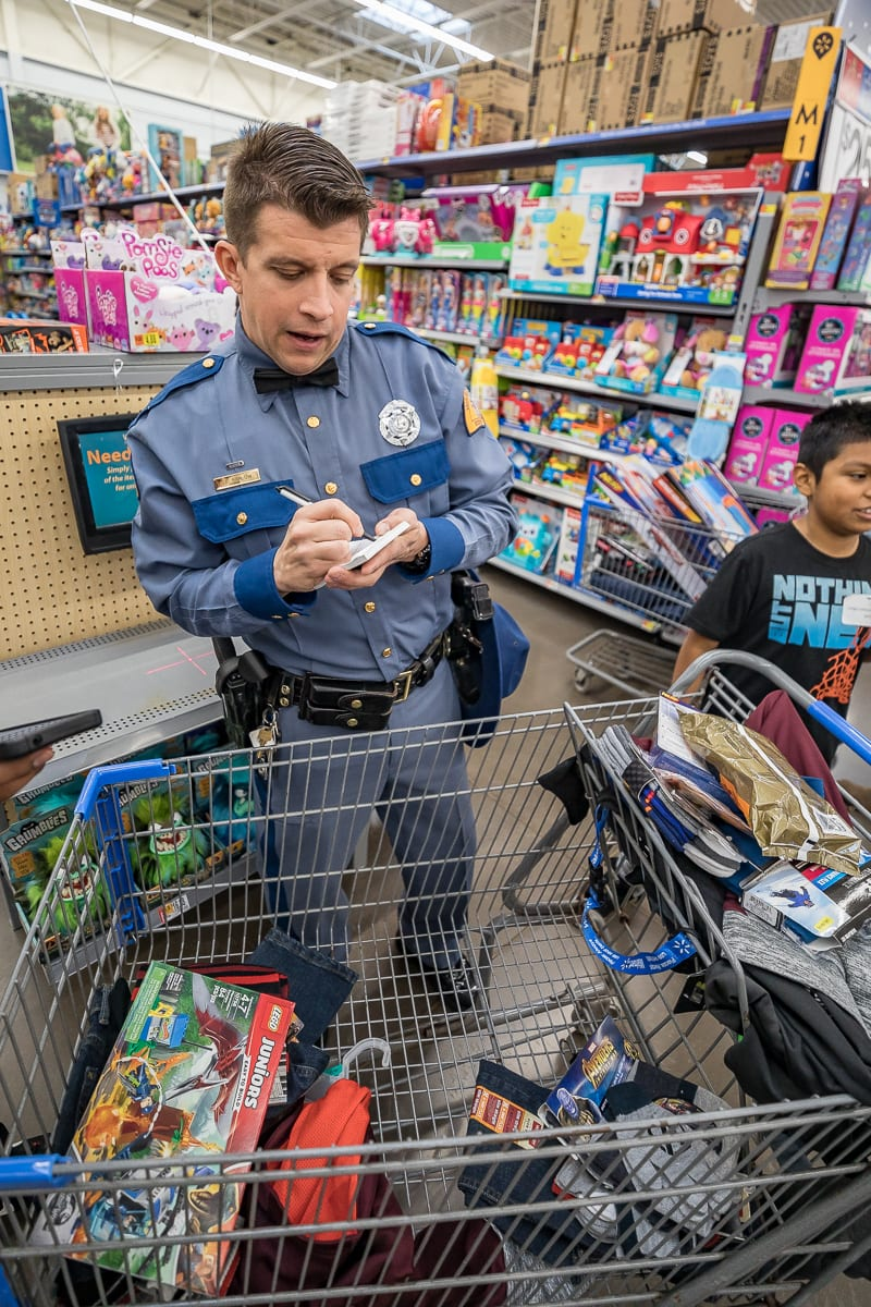 Woodland Police Officer Erik Swenningson helps children find new clothes at this years Shop with a Cop in Woodland. Photo by Mike Schultz