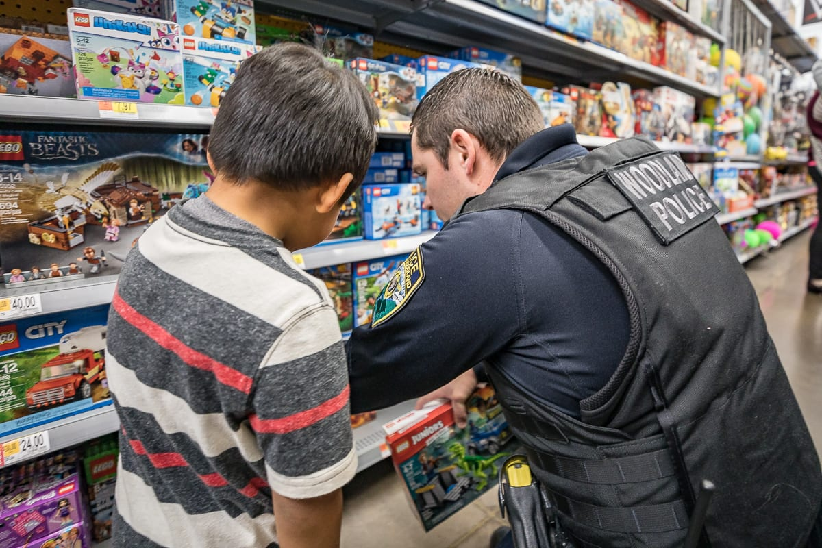 Officer Dustin Palmquist from Woodland Police helps a child find the perfect Lego set for Shop with a Cop 2018. Photo by Mike Schultz