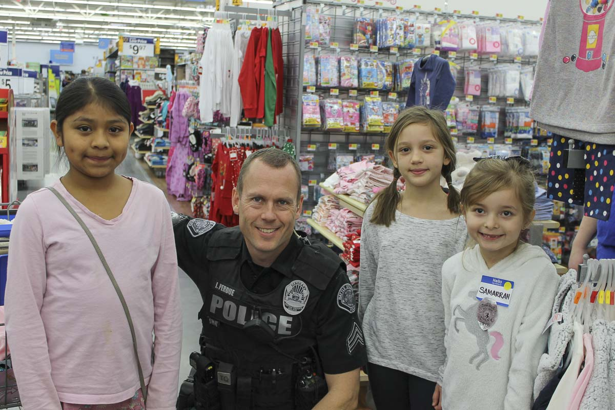 Sgt. Jason Perdue of the Battle Ground Police Department is shown here with children who participated in Battle Ground's Shop with a Cop event. Photo courtesy of city of Battle Ground
