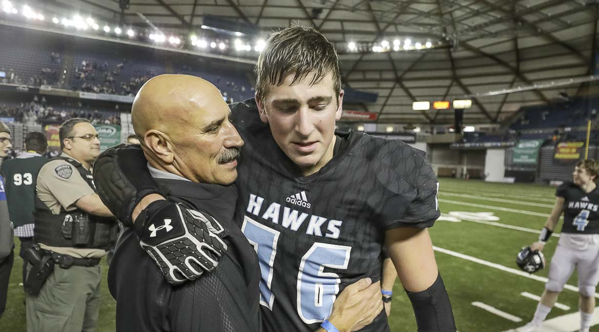 Hockinson head coach Rick Steele (left) congratulates senior lineman Jacob Oldham (76) after the Hawks defeated Lynden 42-37 Saturday in the Class 2A state championship game at the Tacoma Dome. Photo by Mike Schultz