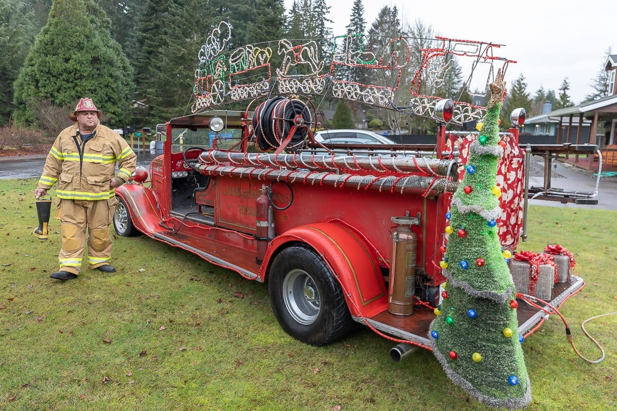 Arnie Kuchta uses his antique fire engine for many Christmas parades as well as collecting donations for Randall Children's Hospital. Photo by Mike Schultz