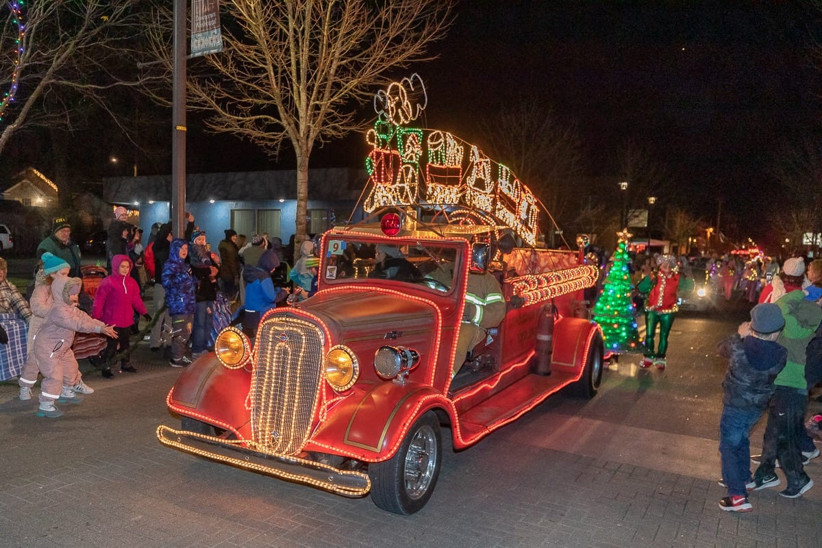 Arnie Kuchta of Battle Ground, drives his lit-up antique fire engine in Washougal's holiday parade in 2018. Photo by Mike Schultz