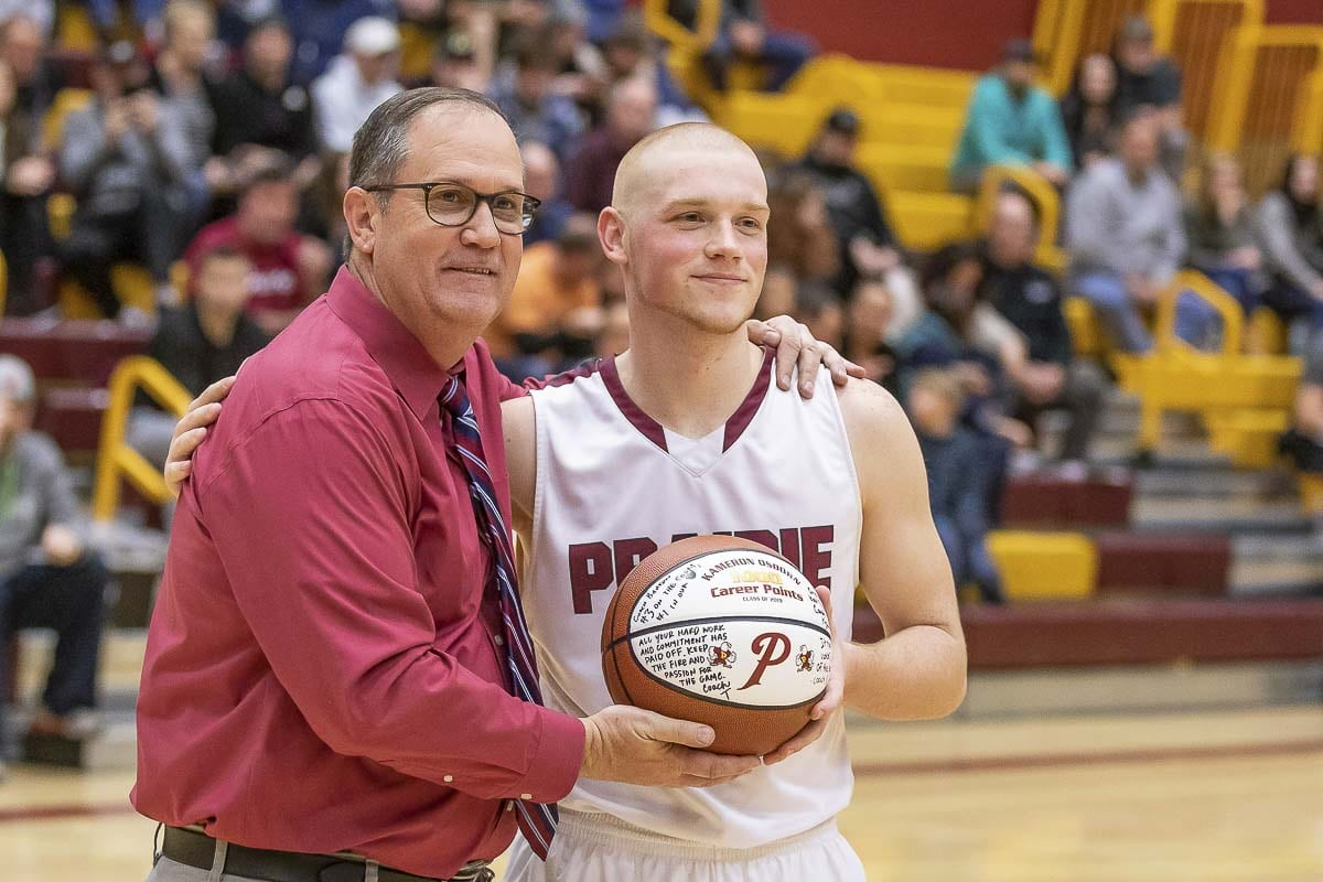Prairie boys basketball coach Kyle Brooks congratulates senior Kameron Osborn during a brief ceremony last week to celebrate Osborn scoring 1,000 points in his career. Photo by Mike Shultz