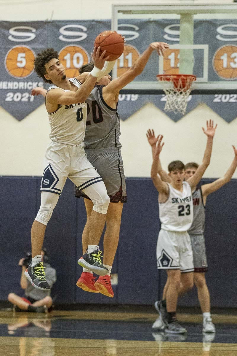 Alex Schumacher (0) of Skyview and Josh Reznick of Union sky high in a battle for a loose ball during Tuesday's Class 4A Greater St. Helens League game. Schumacher scored a game-high 26 points, but it was Union that got the win. Photo by Mike Schultz
