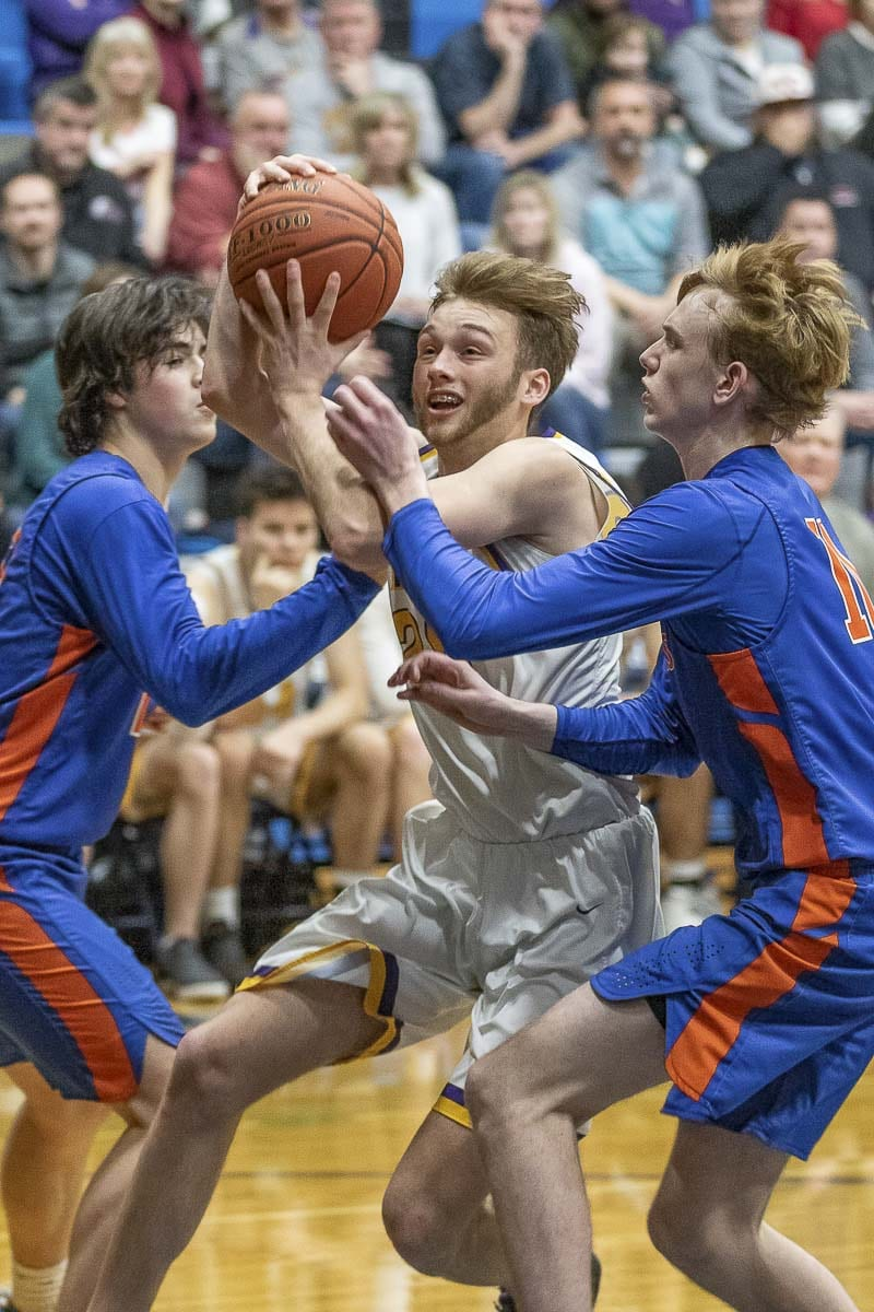 Columbia River's Caden Dezort gets in between two defenders on his way to the basket during River's 65-41 win over Ridgefield on Thursday. Photo by Mike Schultz