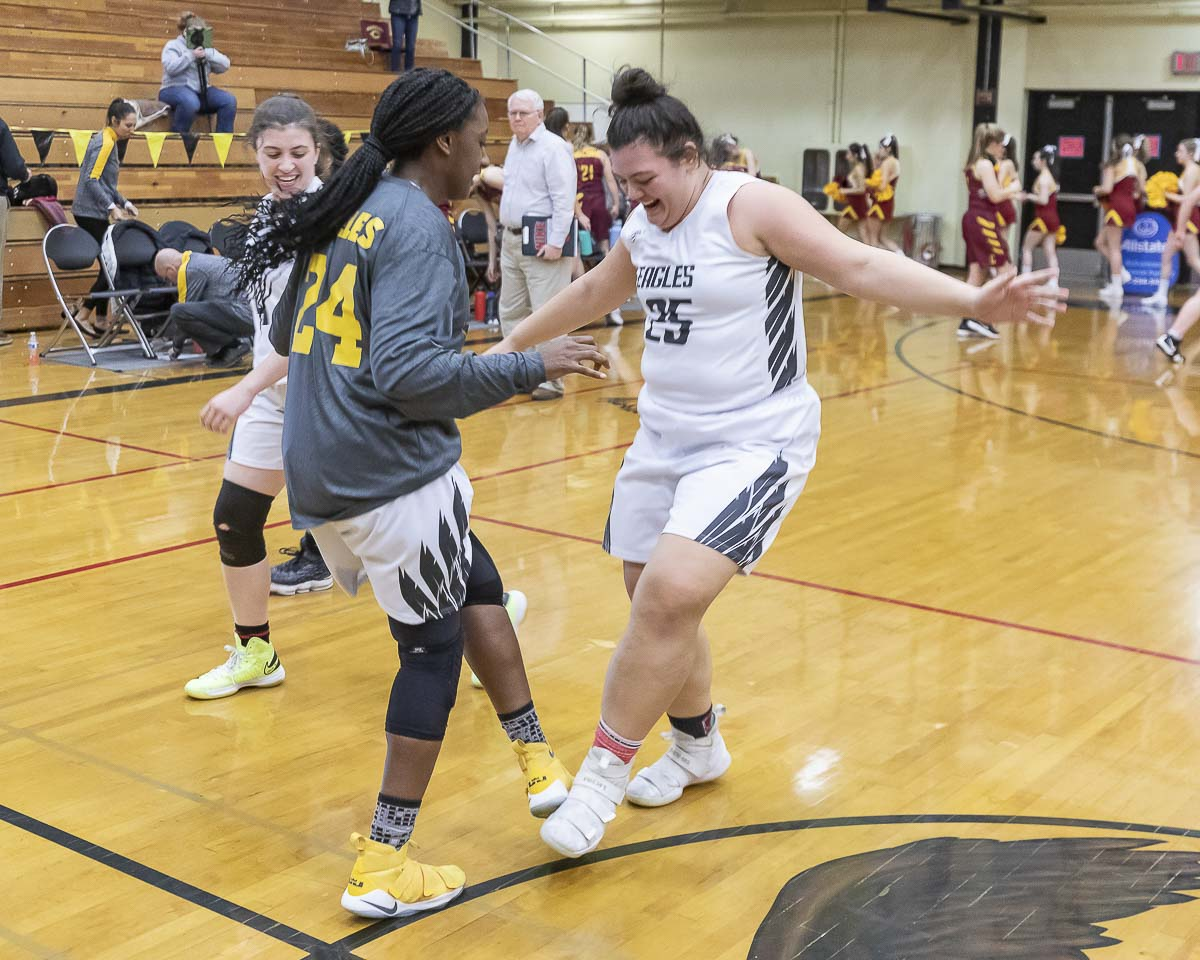 Kamelai Powell, left, and Anastacia Mikaele (25) celebrate as the Hudson's Bay Eagles took care of business, beating Capital 58-44 Thursday. Photo by Mike Schultz