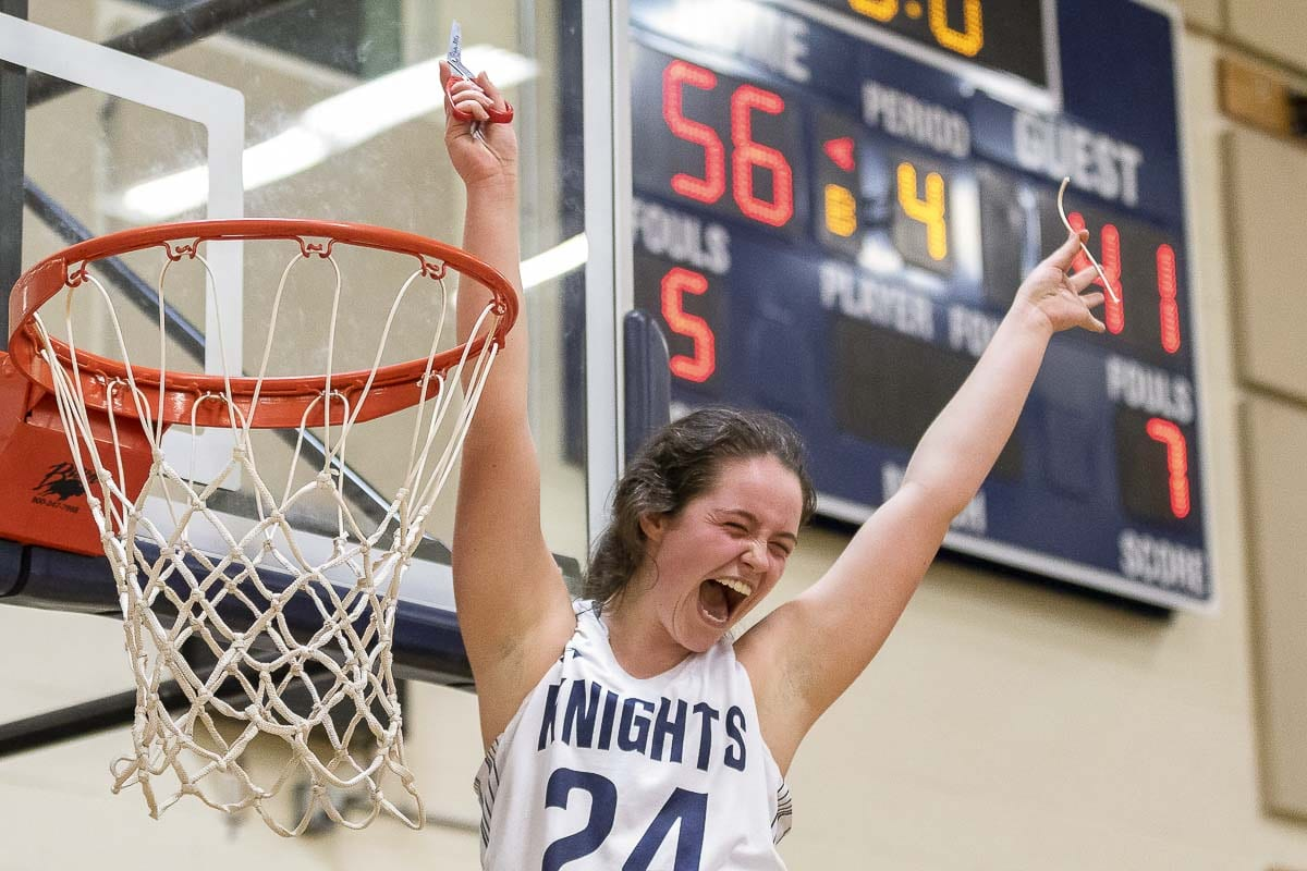 King's Way Christian senior Tyra Schroeder is all smiles after she took her piece of net as the Knights celebrated a perfect Trico League season in girls basketball. Photo by Mike Schultz