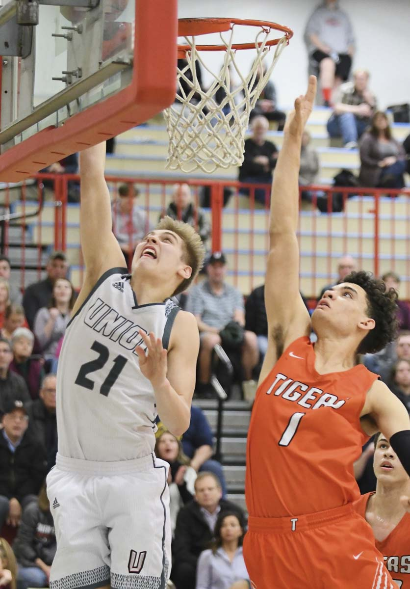 Union's Tanner Toolson goes for two points against Battle Ground's KeAndre Hunter-Holliday in Union's 56-37 win Friday night. Union advanced to the Class 4A state quarterfinals. Battle Ground is still alive, and will play in the state round-of-12 at the Tacoma Dome next week. Photo by Kris Cavin