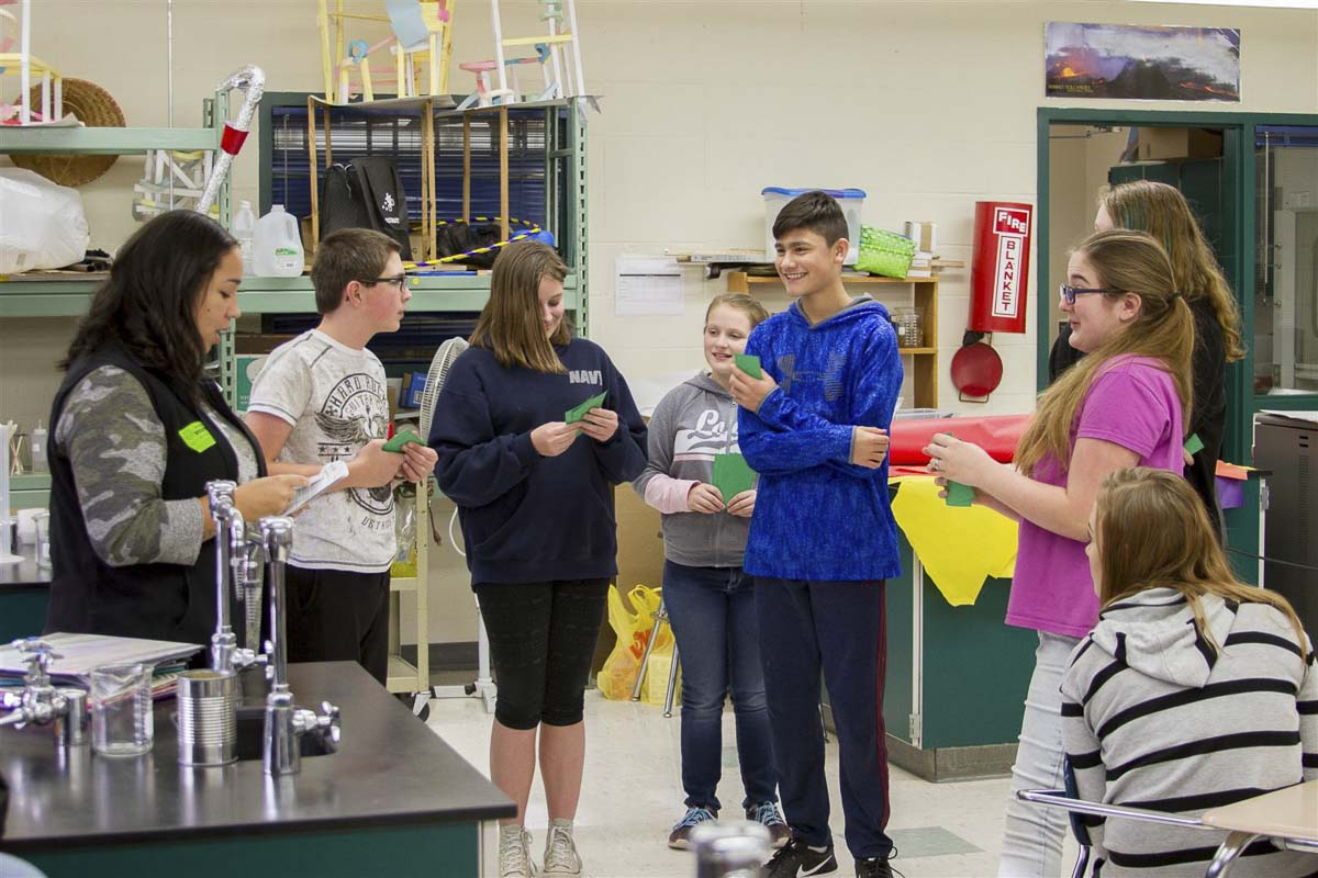 Shantelle Davidson (far left) guides eighth graders at Woodland Middle School through an activity where a student volunteer has to make ends meet with only a minimum wage job after dropping out of school. Photo courtesy of Woodland School District