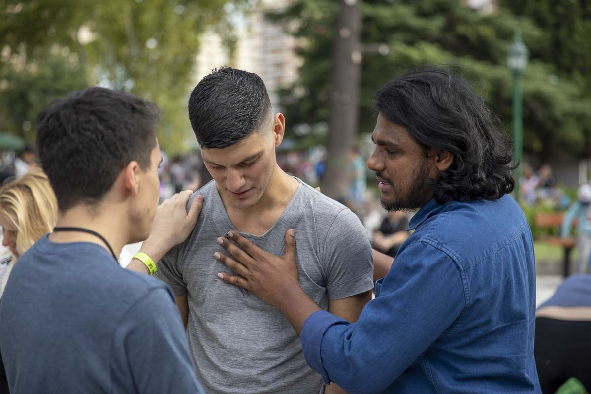 Compassion To Action evangelist, Jonathan Chandra, prays with a man in a park outside Buenos Aires, Argentina to receive Jesus as his savior. Photo by Jacob Granneman, Courtesy of Compassion To Action