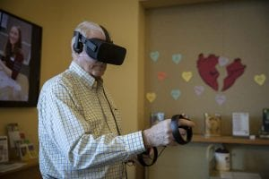 Cliff Anderson uses the Oculus Rift to play a introductory game, made to help beginners understand how to navigate in a virtual reality. Photo by Jacob Granneman