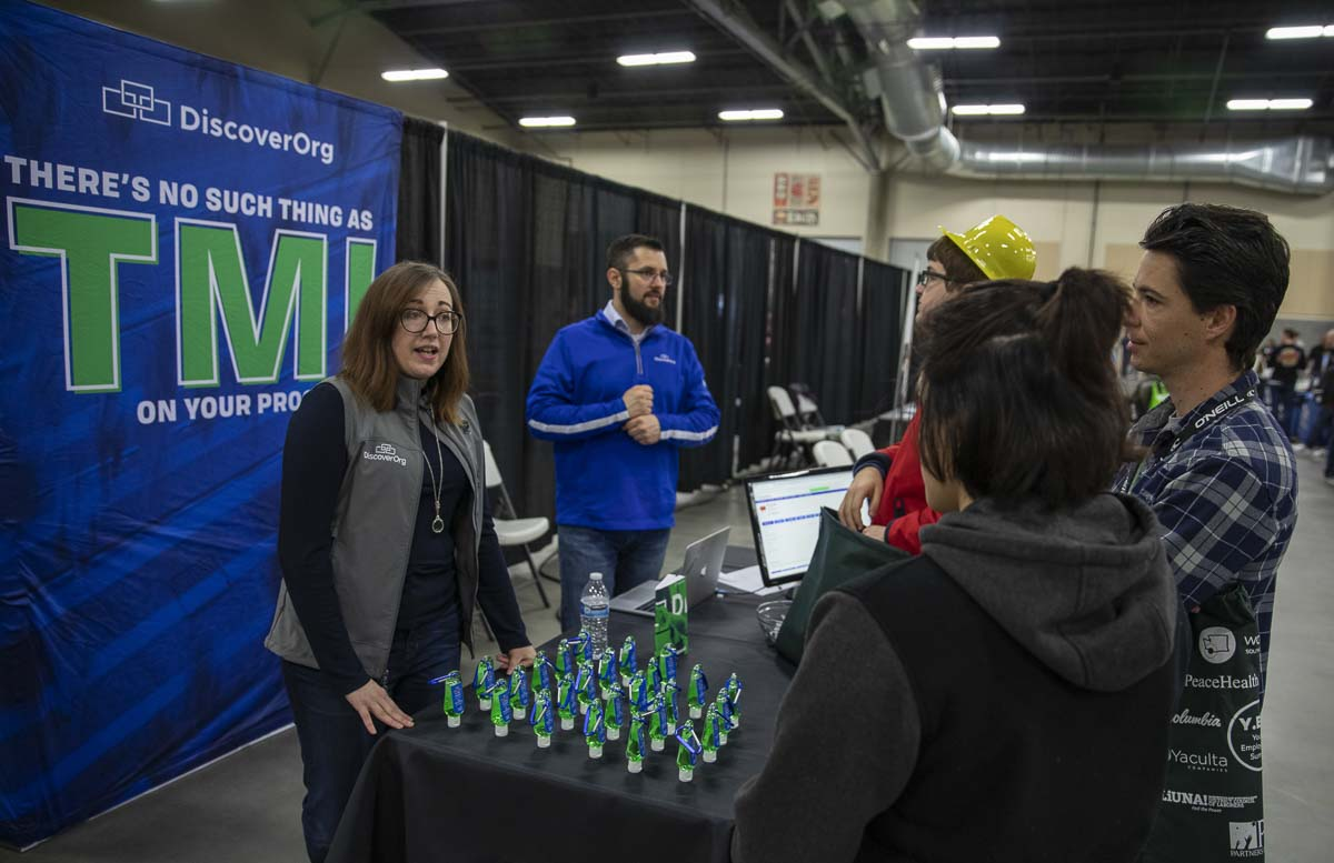 Cassie Harris, (left), and Ben Loria, (right), of Vancouver data company, DiscoverOrg, are seen here interacting with students at their booth during the 2019 Youth Employment Summit. Photo by Jacob Granneman