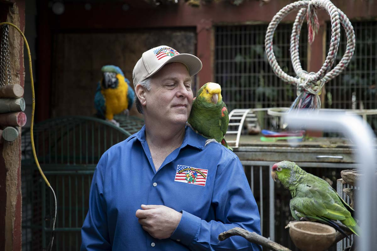 Chris Sandin, a veteran and volunteer with Parrots for Patriots, holds a rescue bird among many exotic parrots inside the aviary at Chris Driggins' bird sanctuary. Photo by Jacob Granneman