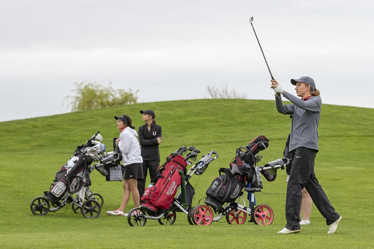 Camas golfer Callie Wengler takes her team's approach shot as Union players Callie Mills and Cassidy Pettitt look on during Monday's Titan Cup. Ashley Clark of Camas is behind Wengler. Clark and Wengler won this match, helping Camas win the Titan Cup for the fourth consecutive year. Photo by Mike Schultz
