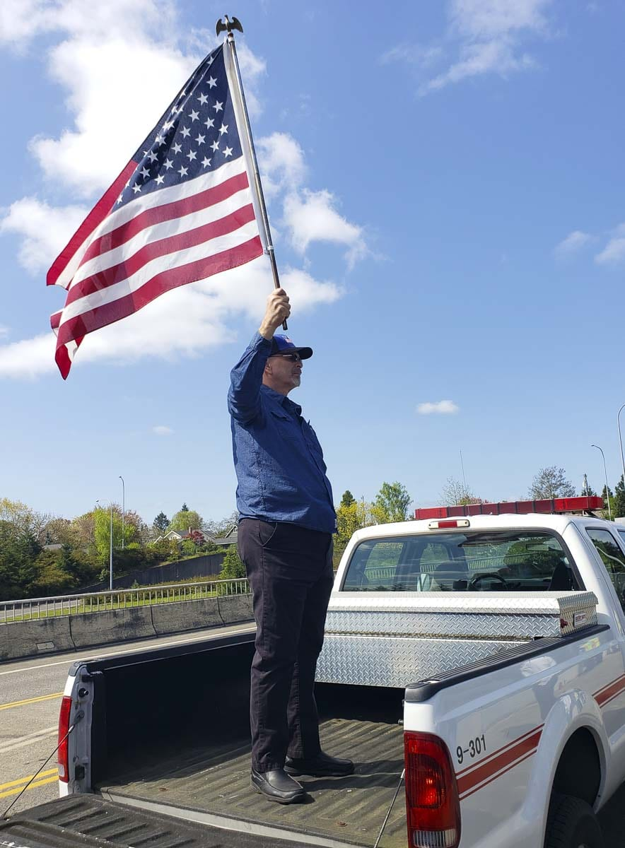 "Mike Kandoll of Vancouver stood tall on the bed of a pick-up truck parked on the 39th Street overpass, holding an American flag as the procession rolled through the city on Interstate 5. ""I just wanted to show my respect for the fallen officer,"" said Kandoll, who spent 35 years in law enforcement. ""I just know how tough the job is and how things can happen without warning. I salute everybody who has chosen this profession, to keep our communities safe."" Photo by Paul Valencia"