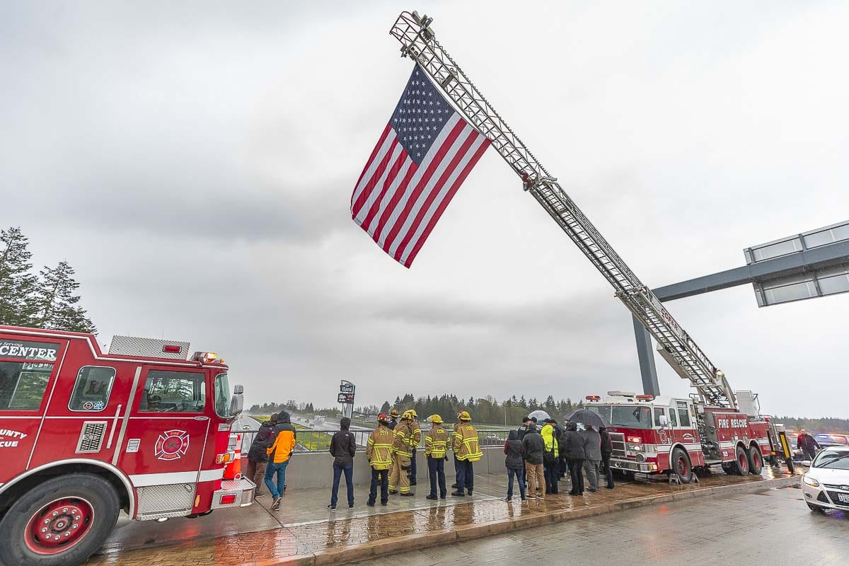 A Clark County Fire and Rescue ladder truck holds an American Flag above the La Center I-5 overpass to show support for Cowlitz County Deputy Justin DeRosier. Photo by Mike Schultz