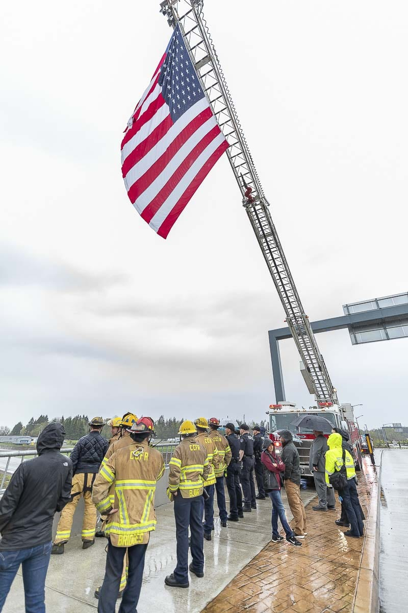 An American Flag is suspended from a Clark County Fire and Rescue ladder truck on the La Center overpass as a procession for fallen Cowlitz County Deputy Justin DeRosier passes on the freeway below. Photo by Mike Schultz