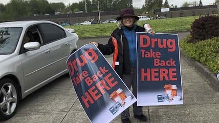 A volunteer holds signs at a 2018 Drug Take-Back event. Photo courtesy of Educational Service District 112