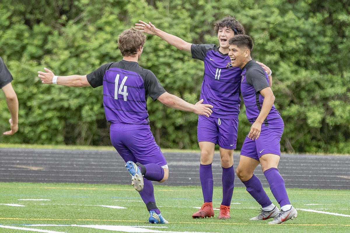 Columbia River's Sideras Kosaris (11) is being hugged by teammate Aaron Espinosa as they await Jake Connop, who is on his way to join the celebration. Kosaris put Columbia River ahead 1-0 in the state quarterfinals. Photo by Mike Schultz