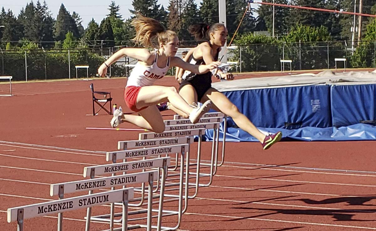 Union's Annaliese Ward battles with Ella Wilks of Camas in the 300 hurdles Thursday at the Class 4A district track and field meet. Ward would go on to win the title. Photo by Paul Valencia