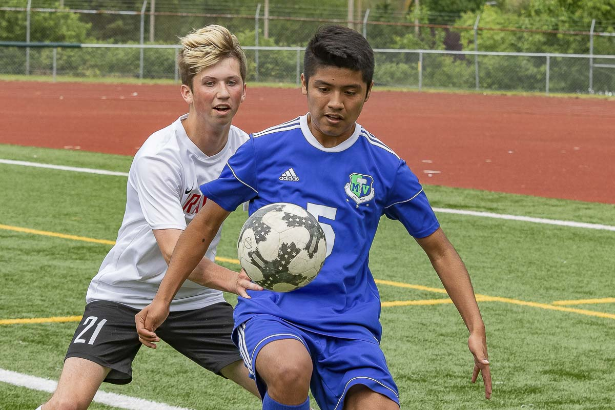 Melvin Ramir (5) of Mountain View is focused on keeping control of the ball while fending off a Kamiakin defender Saturday during their playoff match. Mountain View won 2-0. Photo by Mike Schultz