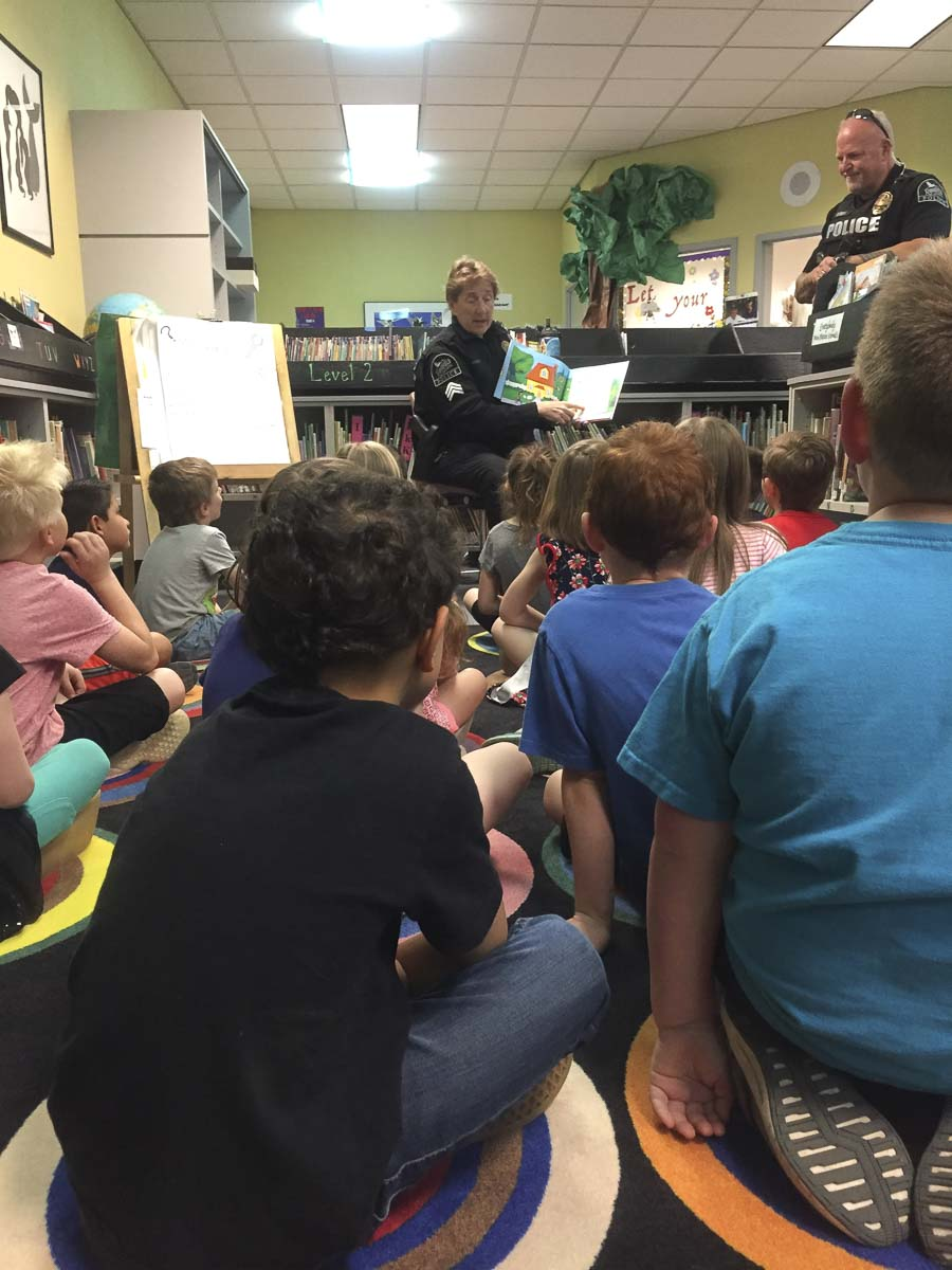 Kindergartners at Union Ridge Elementary enjoy a reading visit from Ridgefield police officers, Sergeant Cathy Doriot and Officer Jason Ferriss earned as part of the library's PBIS reward program. Photo courtesy Ridgefield School District