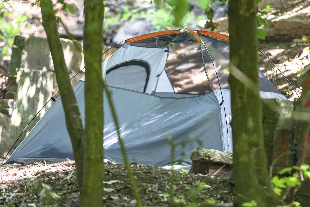 A tent marks one of several homeless camps in a wooded piece of property south of the Homeless Navigation Center on Grand Avenue. Photo by Mike Schultz