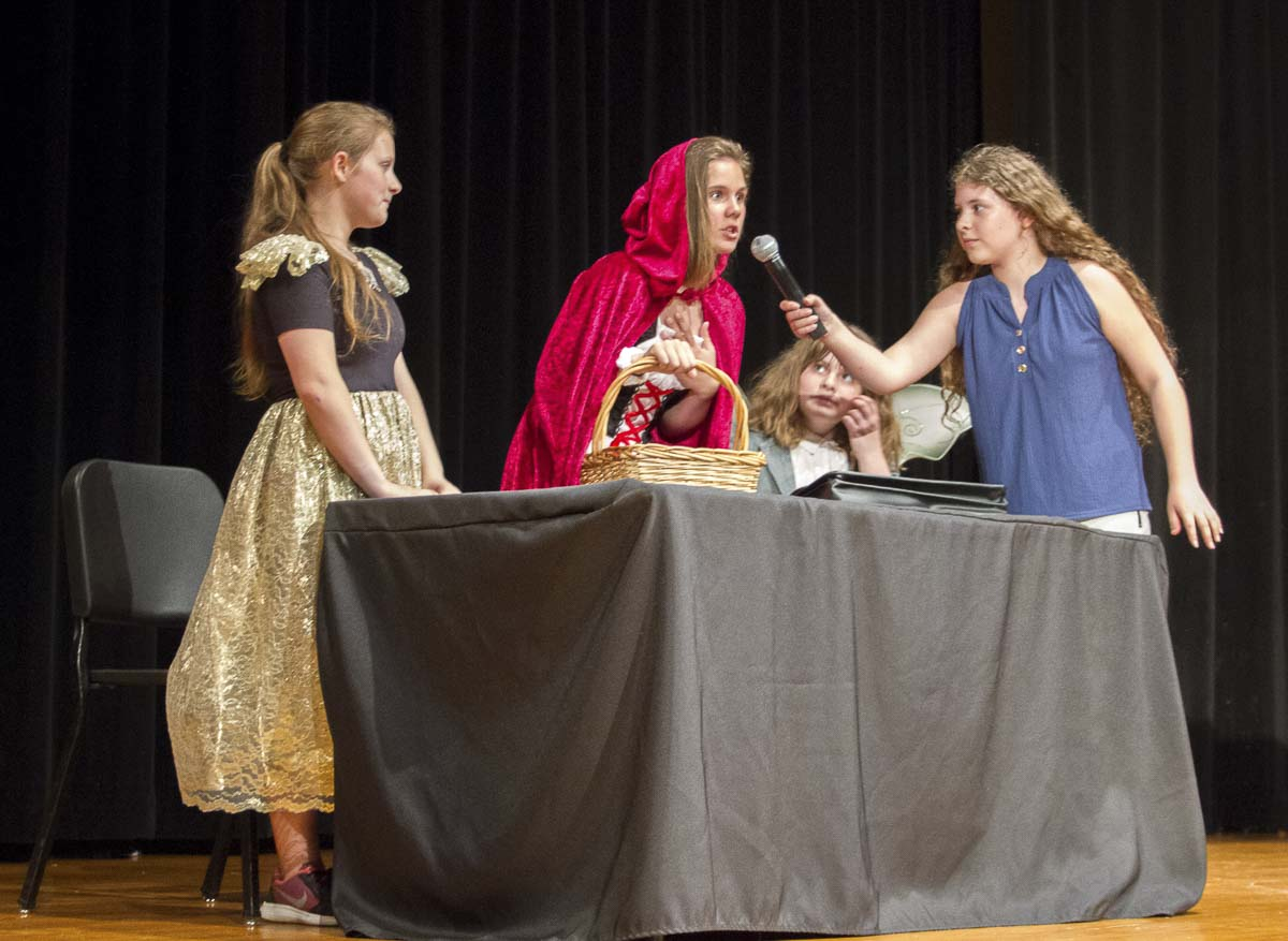 Calista Conder plays a journalist interviewing Little Red Riding Hood, played by Savannah Doughty with Grandmother Hood played by Caitlin Nelson looking on. Photo courtesy of Woodland School District