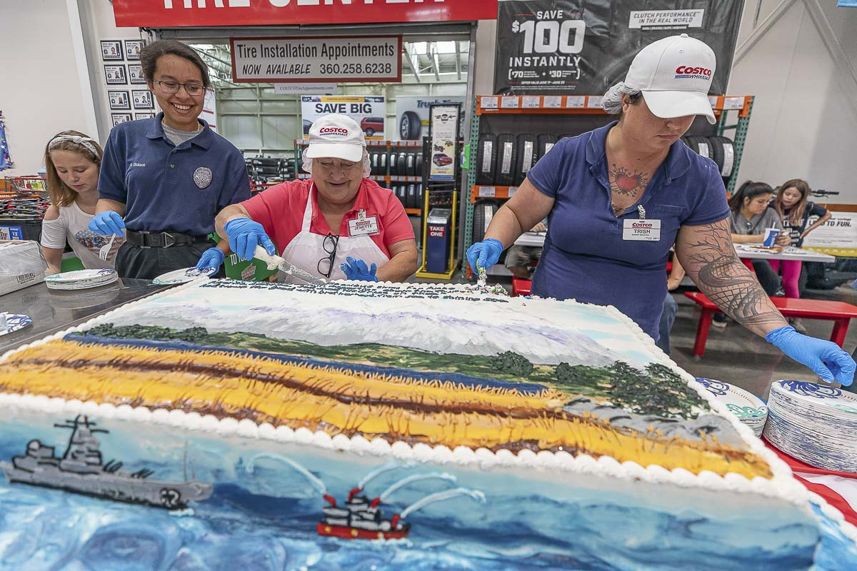 Katherine Dickson, Jenette Paul, and Trish Hollingsworth prepare to serve pieces of America the Beautiful cake at Heroes Night at the east Vancouver Costco on Saturday night. Photo by Mike Schultz