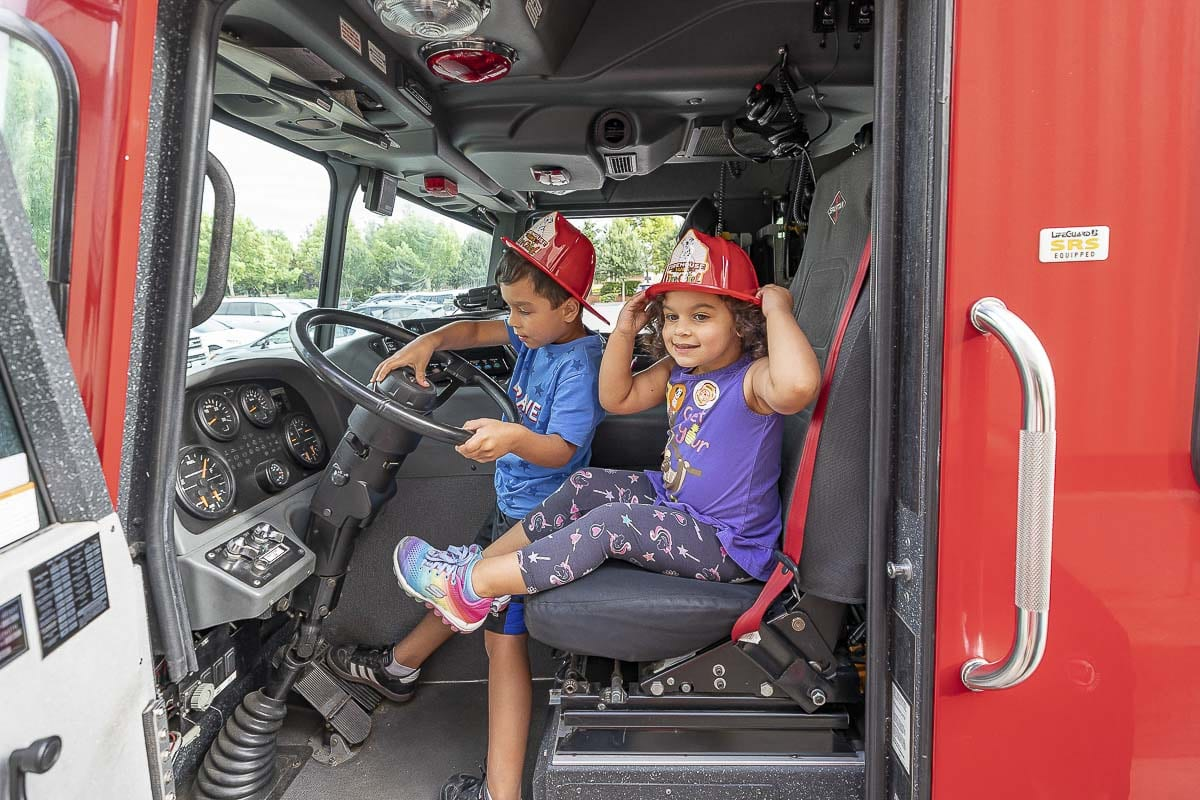Mac and Caline Shipp get a chance to sit in a Camas-Washougal Fire Department vehicle during Heroes Night on Saturday at the east Vancouver Costco. Photo by Mike Schultz